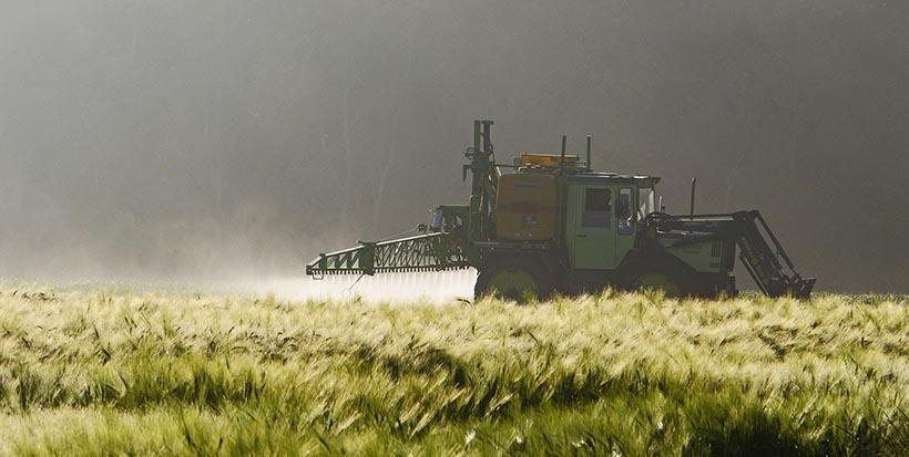 Tracteur difusant des pesticides dans un champs.