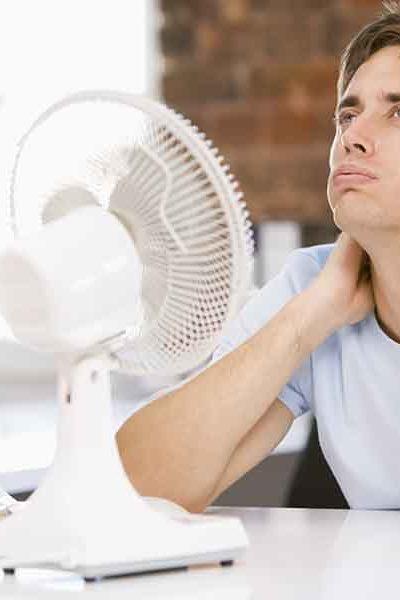 Homme, prenant le frais avec un ventilateur.