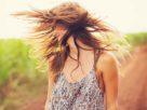 Femme en robe courte dans les champsavec des cheveux longs volant dans le vent.