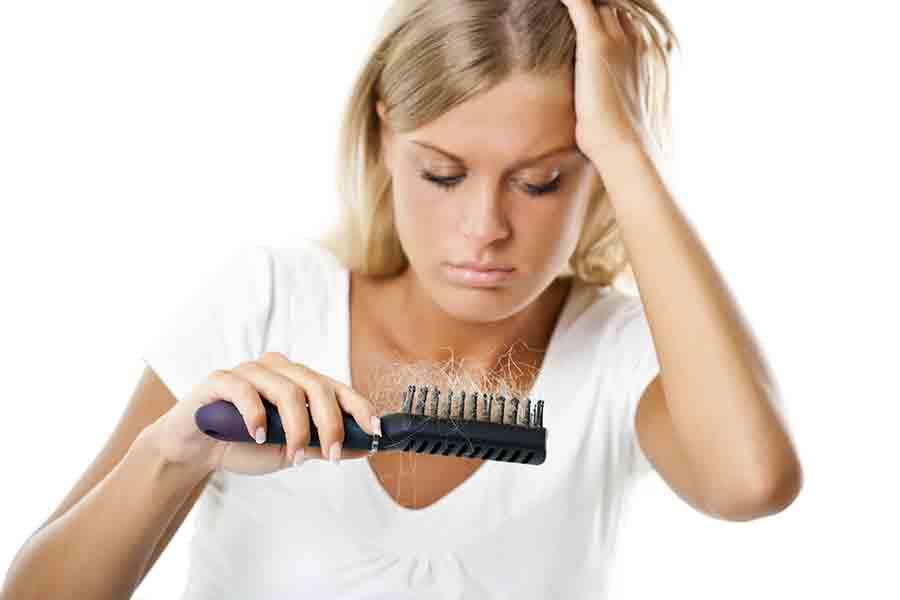 Femme regardant sa brosse à cheveux.