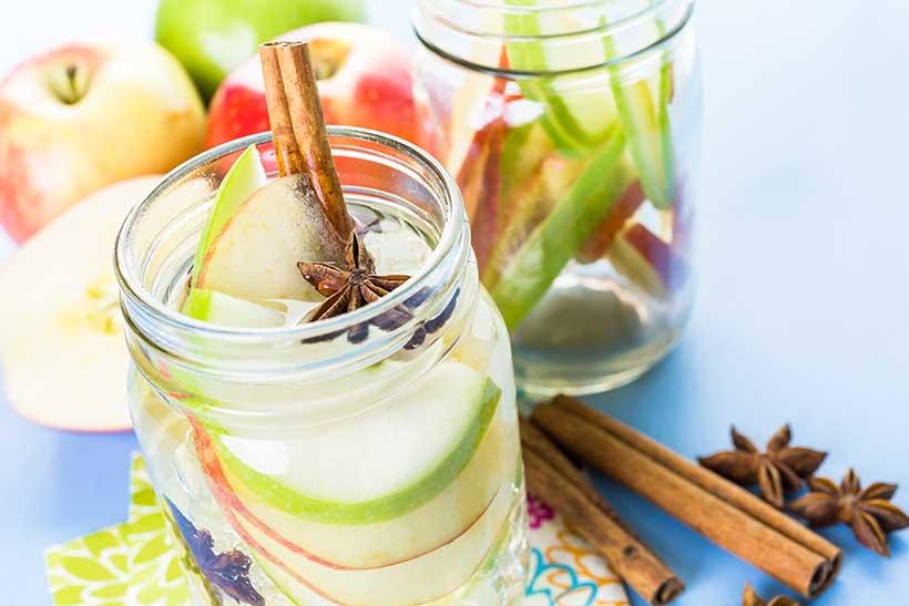 Eau infusée de pomme et de cannelle en pichet prêt à boire.