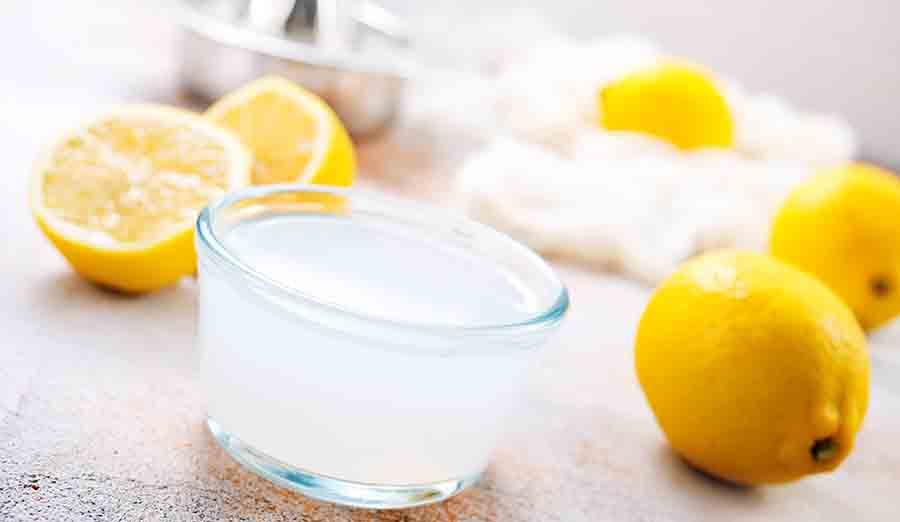 Jus de citron dans un verre et demi-citrons coupés en deux sur une table