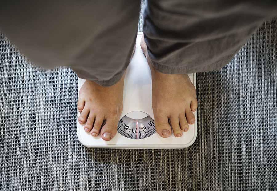 Une personne se pése pour connaître son poids.