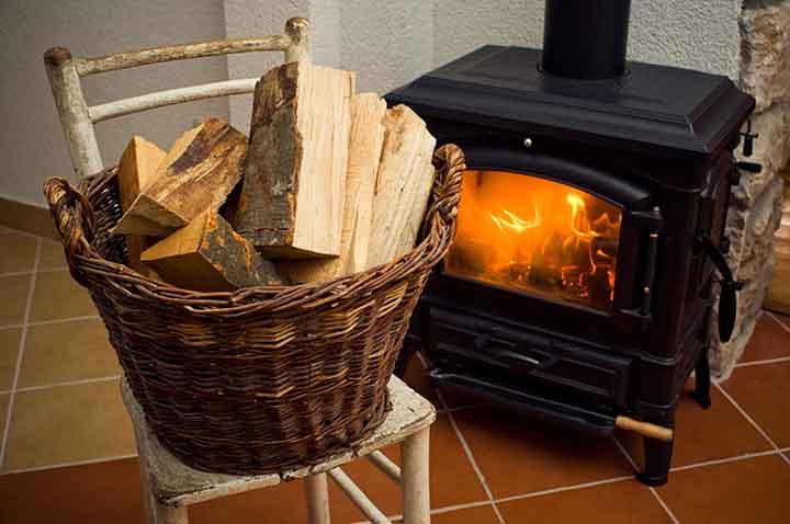 Panier de bûches de bois à coté d'un poêle.