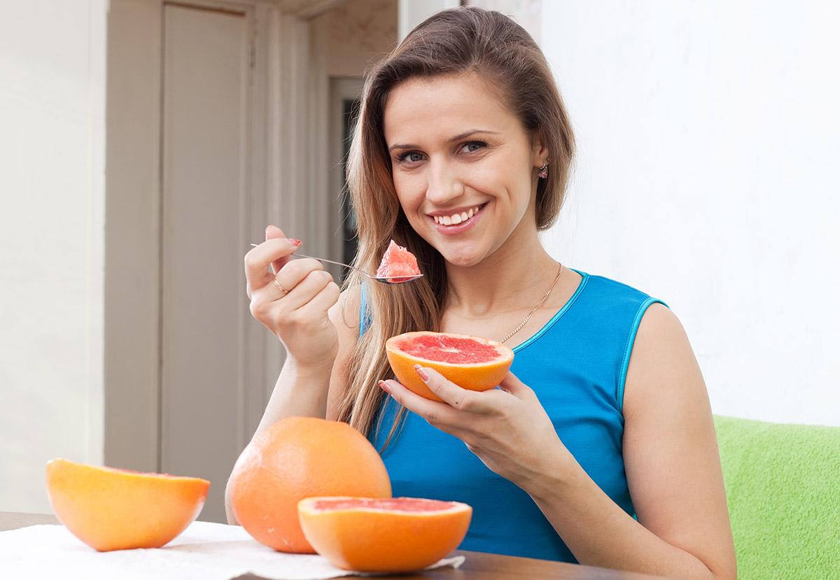 Une personne mange un fruit détoxifiant.