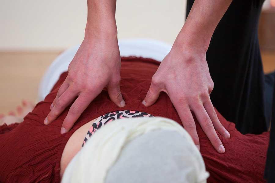Massage shiatsu avec les mains sur une patiente.
