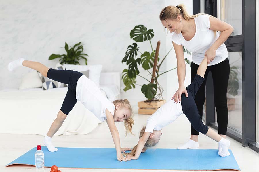 Deux enfants faisant du sport avec leur mére à la maison.