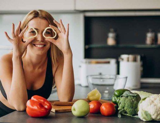 Jeune femme sportive avec des légumes dans la cuisine