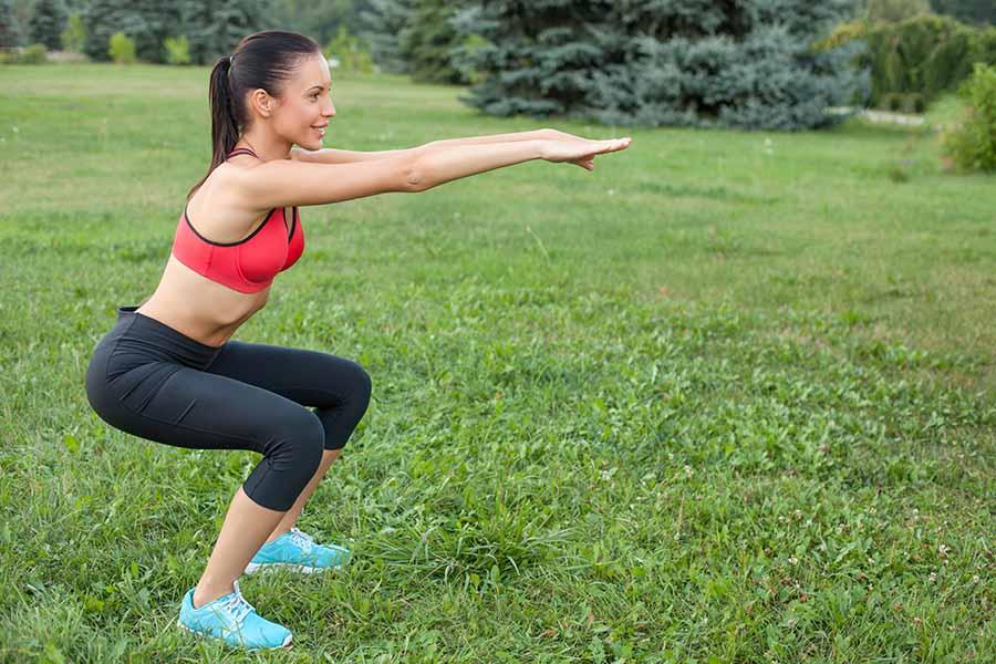 Femme faisant des squats pour tonifier les fessiers.